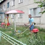 В доме № 16 по улице Восточной 16 квартир.  Скосить траву в палисаднике вышел Владимир Кручинин.  Косит, разумеется, не только под своим окошком.